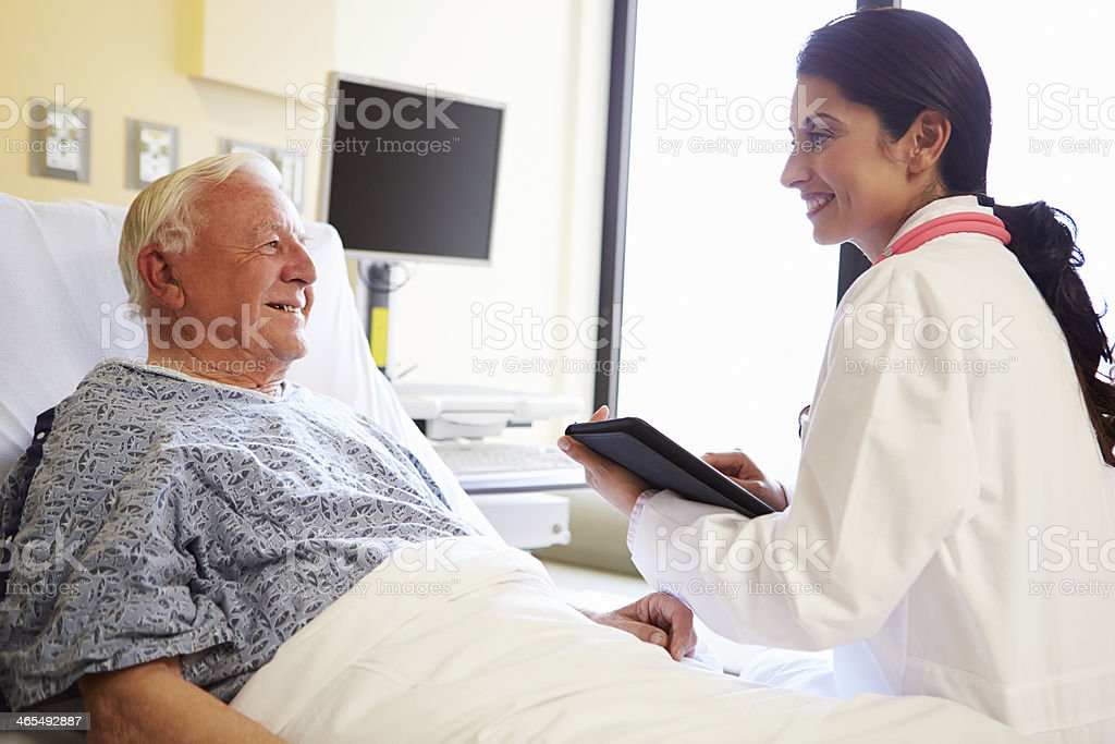 Doctor With Digital Tablet Talking To Patient In Hospital stock photo