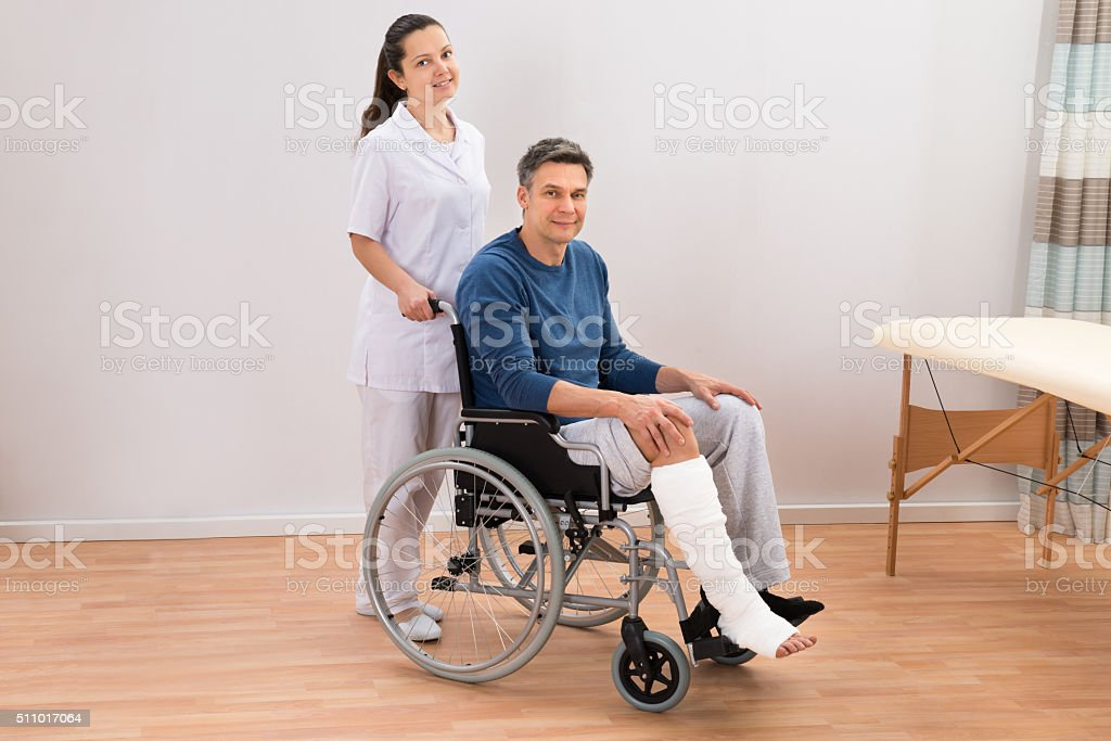 Doctor With Disabled Patient On Wheelchair stock photo