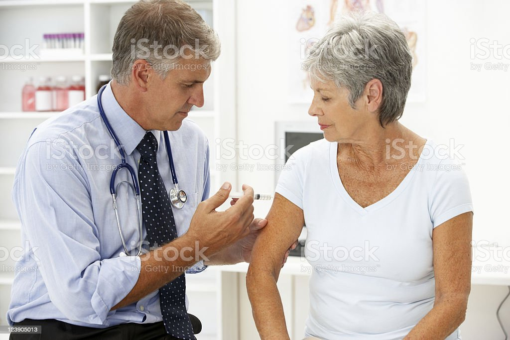Doctor with female patient giving her an injection stock photo