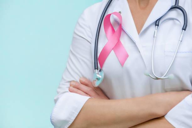 o doutor com braços dobrados e um estetoscópio em sua garganta, mostra um close-up cor-de-rosa da fita no uniforme - outubro rosa - fotografias e filmes do acervo