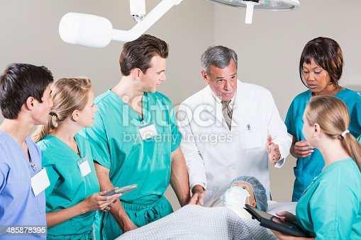 Doctor (60s) talking with group of medical students, with dummy on operating table.