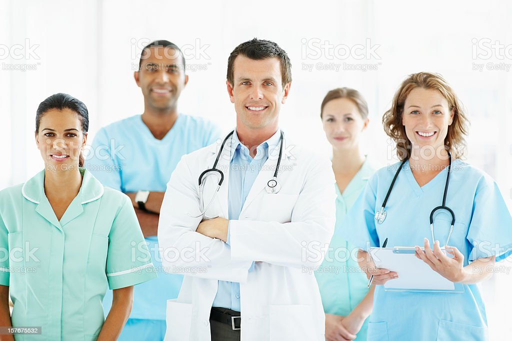 Doctor with hands folded standing in front of team royalty-free stock photo