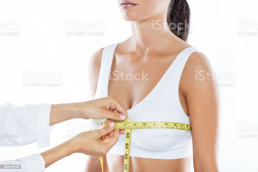 Doctor with measure tape measuring the size of the patient's breast. stock photo