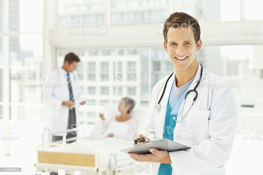 Doctor with Medical Chart in a Hospital Room royalty-free stock photo