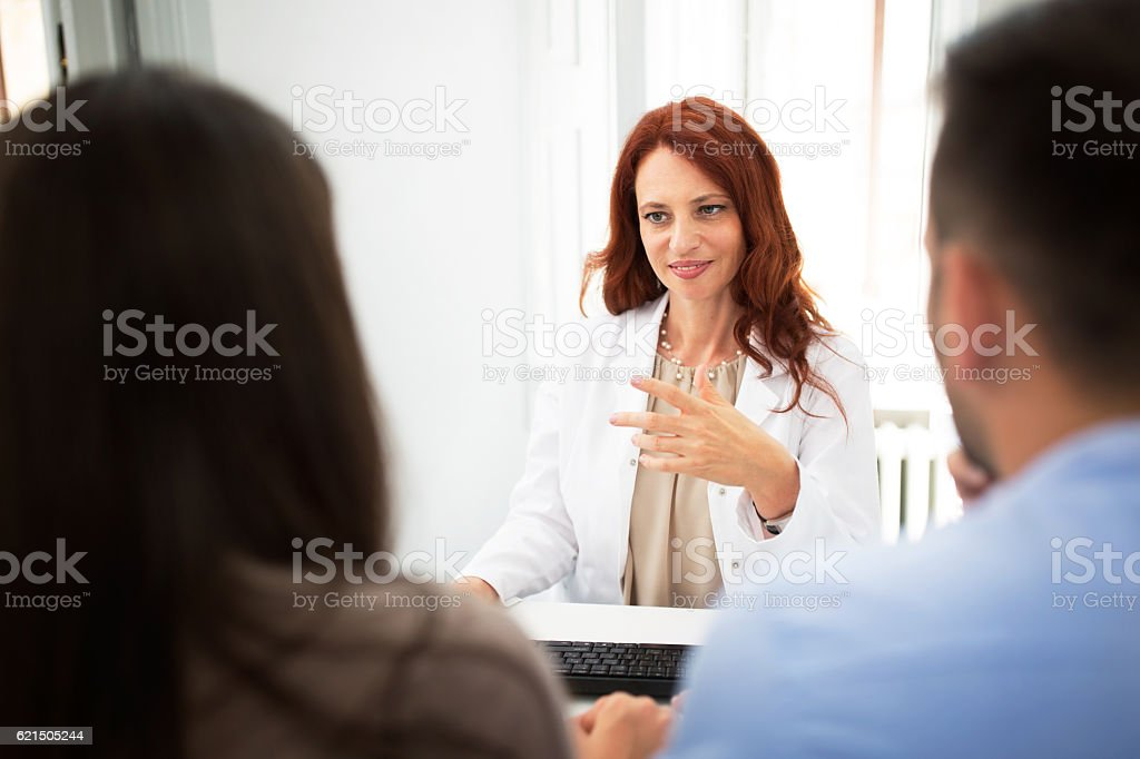 Doctor with patients talking at clinic Lizenzfreies stock-foto