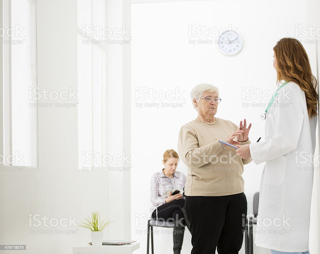 Doctor with senior woman in waiting room. stock photo