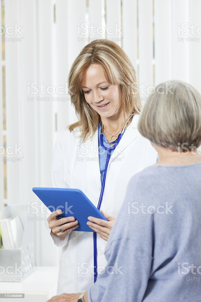 Doctor with Senior Woman Patient in Medical Office Vt royalty-free stock photo