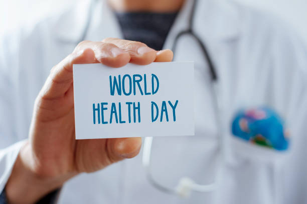 doctor with signboard with text world health day closeup of a young caucasian doctor man, with a world globe in the pocket of his white coat, showing a signboard with the text world health day written in it world health day stock pictures, royalty-free photos & images
