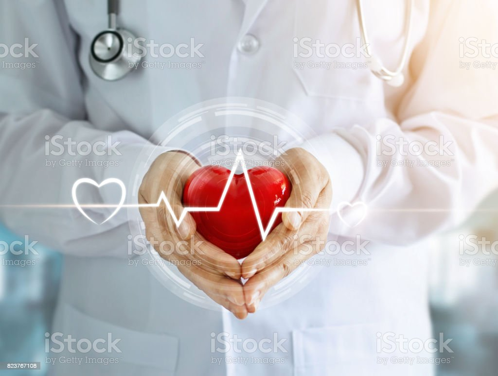 Doctor with stethoscope and red heart shape with icon heartbeat in hands on hospital background stock photo