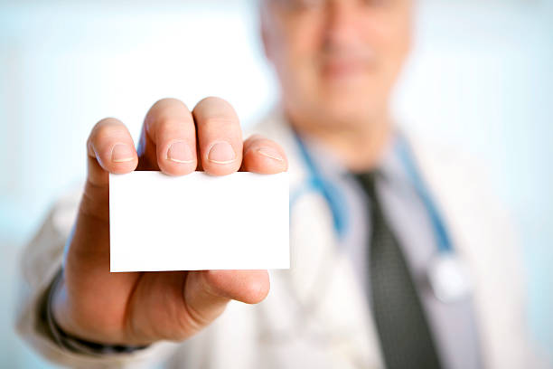 Doctor with stethoscope around his neck showing a blank card stock photo