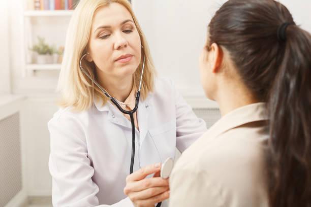 arts met de stethoscoop controle patiënten hart beat - basisschool stockfoto's en -beelden