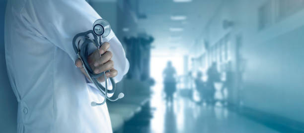 Doctor with stethoscope in hand on hospital background stock photo