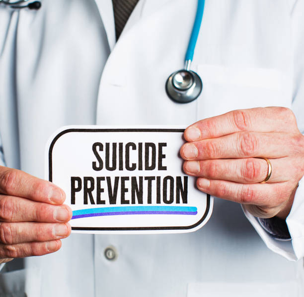 Doctor with stethoscope in white lab coat holding sign reading suicide prevention Doctor with stethoscope in white lab coat holding sign reading suicide prevention suicide stock pictures, royalty-free photos & images