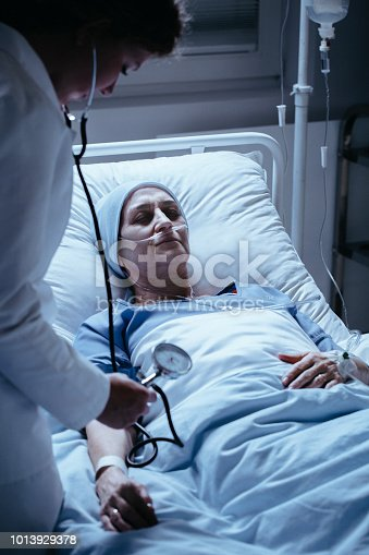 928968772 istock photo Doctor with stethoscope measuring patient's pressure in the hospital 1013929378