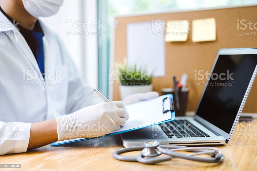 Doctor with stethoscope writing note result in hospital concept - clinic heath care equipment tool in lab with laptop computer stock photo