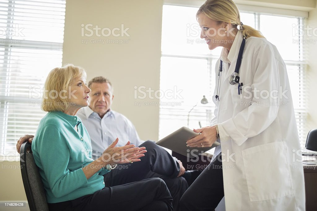 Female doctor with digital tablet discussing medical exam results...