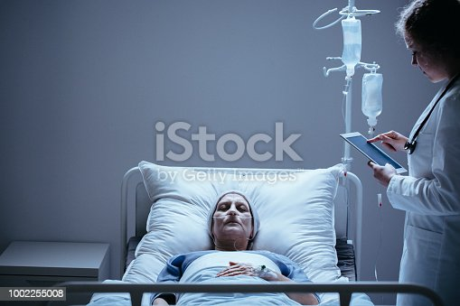 928968772 istock photo Doctor with tablet next to bed with dying elderly woman with cancer in the clinic 1002255008