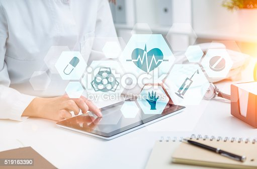 Doctor sitting at table and working with tablet. Medical icons in hexagonals in front. Only hands seen. Concept of medical help.
