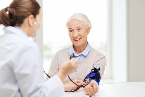 doctor with tonometer and senior woman at hospital medicine, age, health care and people concept - doctor with tonometer checking happy senior woman blood pressure level at hospital hypertensive stock pictures, royalty-free photos & images
