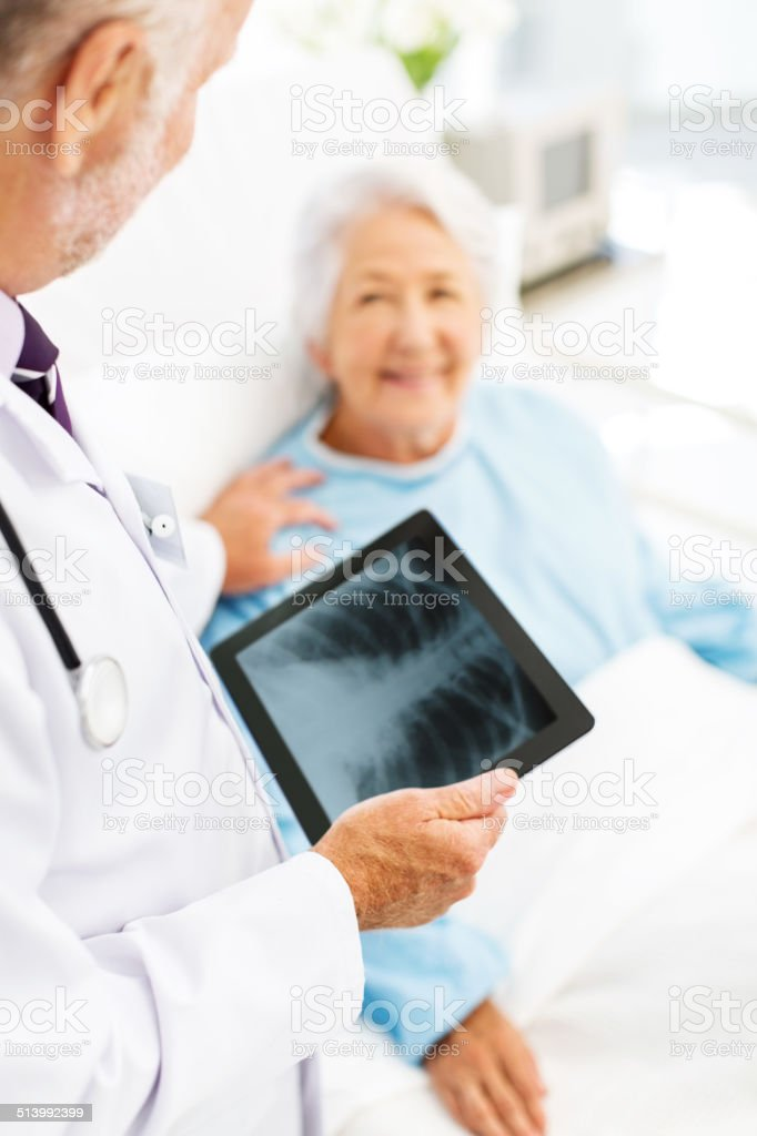 Male doctor with X-ray on digital tablet consoling senior female...