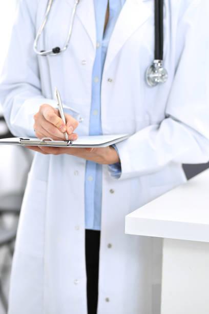 arztfrau füllt medizinisches formular aus, während sie in der nähe der rezeption in der klinik oder in der notfallklinik steht. unbekannter arzt bei der arbeit, hände dicht. medizin und gesundheitskonzept - kindergeldantrag stock-fotos und bilder