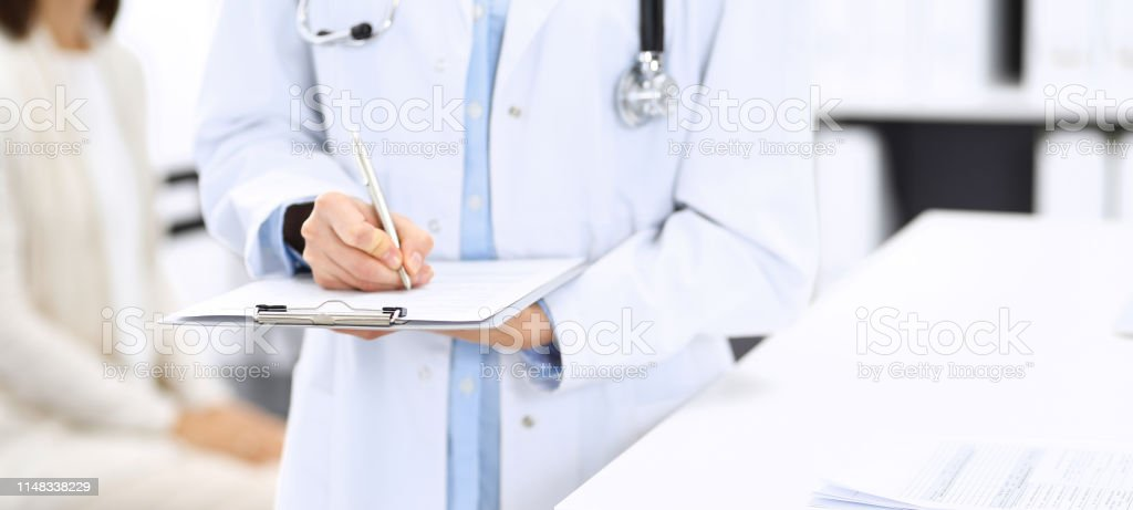 Doctor woman filling up medical form while standing near reception...