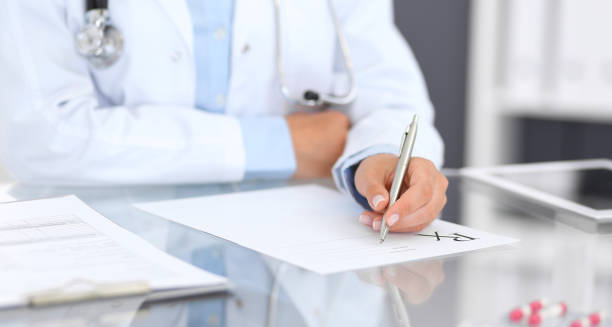doctor woman filling up prescription form while sitting at the desk in hospital close-up.  physician at work and ready to give an advice to help patient. healthcare, insurance and excellent service in medicine concept - prescription stock photos and pictures