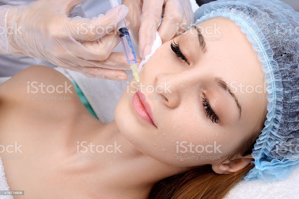 Doctor woman giving botox injections. stock photo