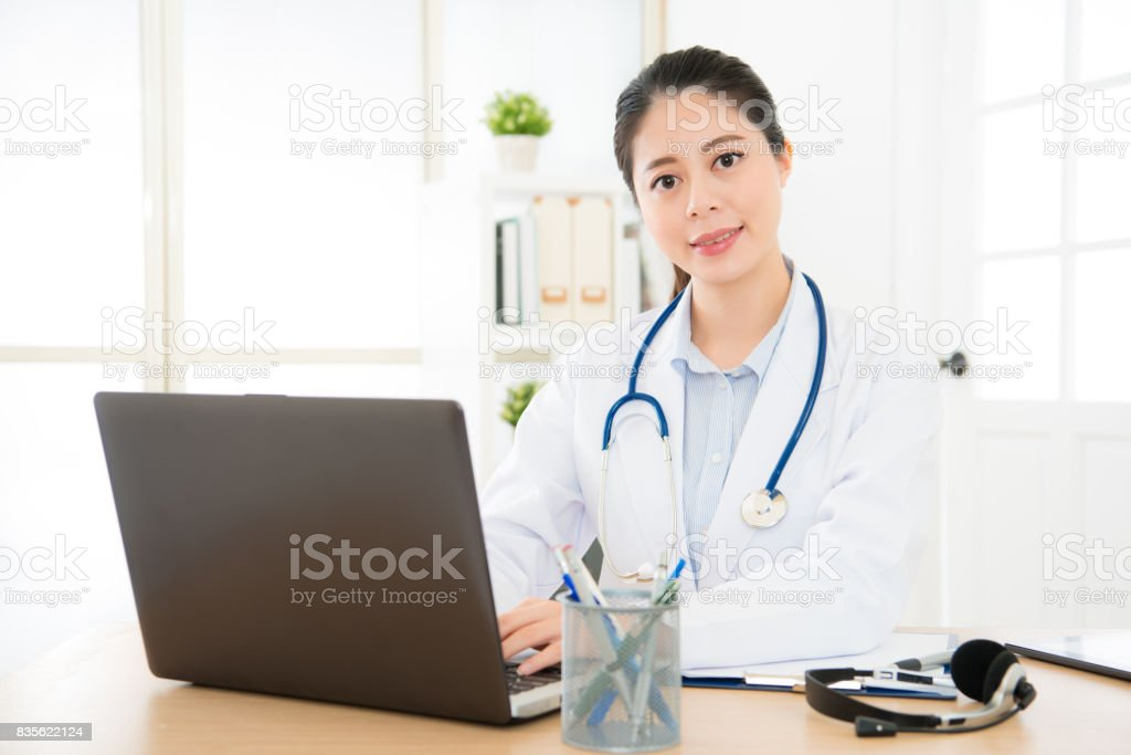 doctor woman typing with laptop system stock photo