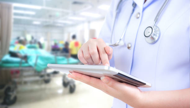 Doctor woman using tablet computer on blurred patient in emergency  room use  hospital background Doctor woman using tablet computer on blurred patient in emergency  room use  hospital background outpatient stock pictures, royalty-free photos & images