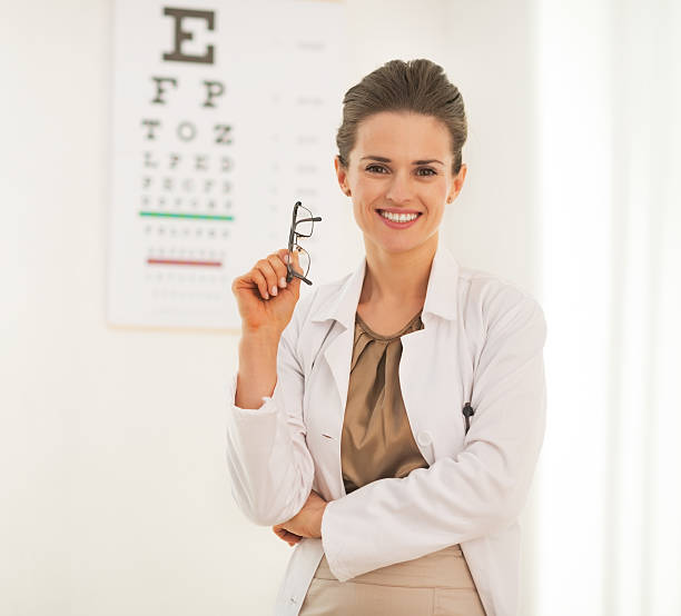 Doctor woman with eyeglasses in front of snellen cha stock photo