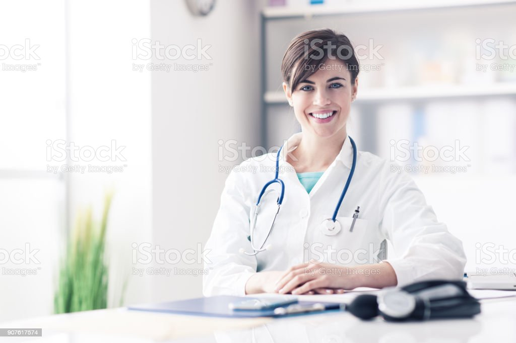 Doctor working at office desk stock photo