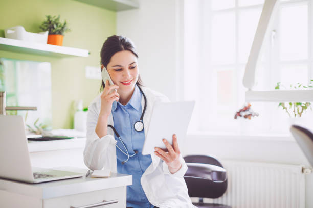 doctor working in her office - nurse on phone stock photos and pictures
