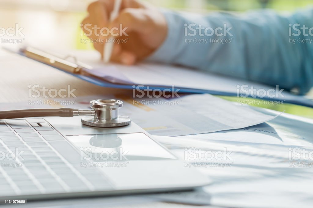 Doctor working in hospital writing prescription clipboard, working an Laptop on desk in hospital with report analysis, Healthcare and medical concept, selective focus - Стоковые фото Анализировать роялти-фри