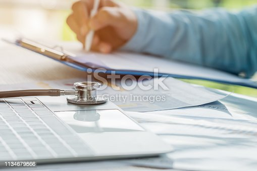 istock Doctor working in hospital writing prescription clipboard, working an Laptop on desk in hospital with report analysis, Healthcare and medical concept, selective focus 1134679866