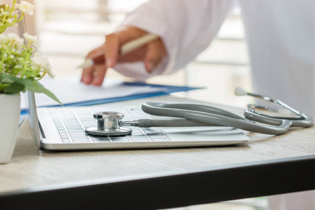 Doctor working in hospital writing prescription clipboard, working an Laptop on desk in hospital with report analysis, Healthcare costs and fees in medical hostpital office stock photo