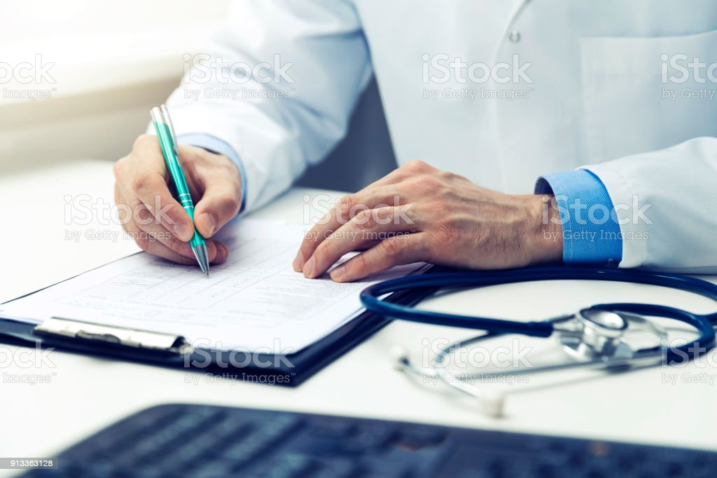 doctor working in office writing documents stock photo