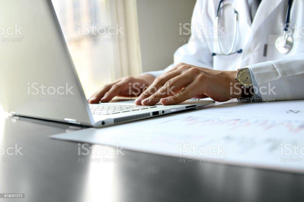 auf einem Computer in seinem Kabinett tätiger Arzt – Foto