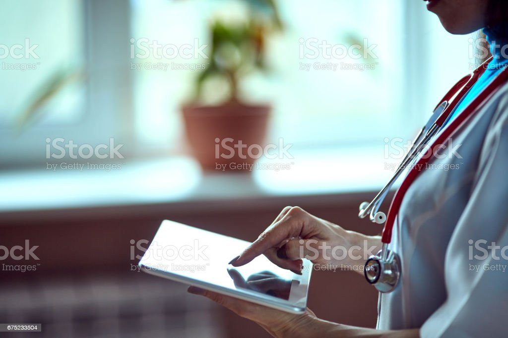 Doctor working on a digital tablet with copy space stock photo