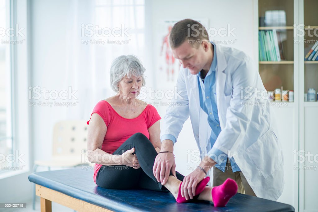 Doctor Working on a Woman's Ankle stock photo
