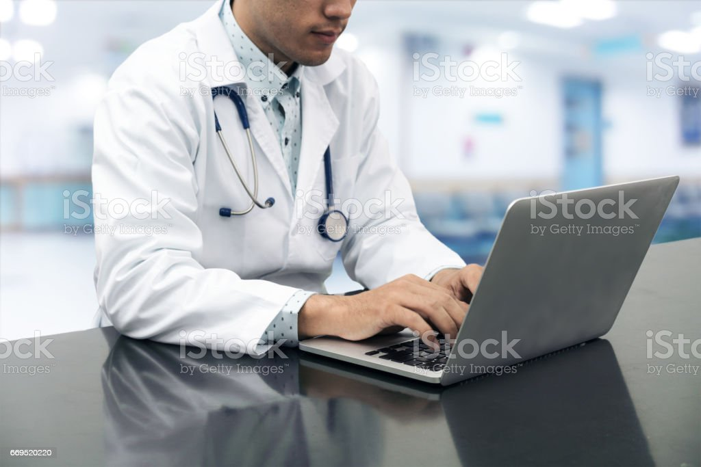 Doctor working on desk with laptop stock photo
