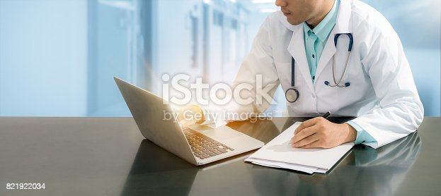 istock Doctor working on desk with laptop 821922034