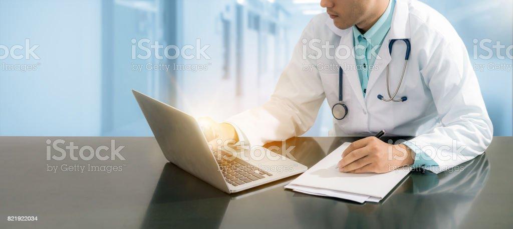 Médico, trabalhando na mesa com o laptop - foto de acervo