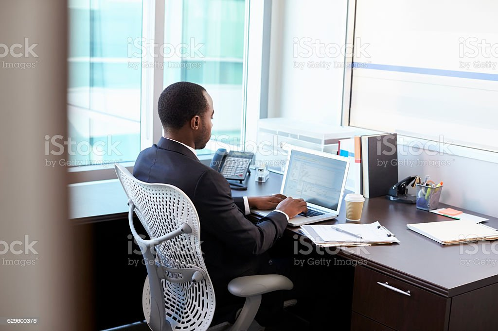 Doctor Working On Laptop At Desk In Office stock photo