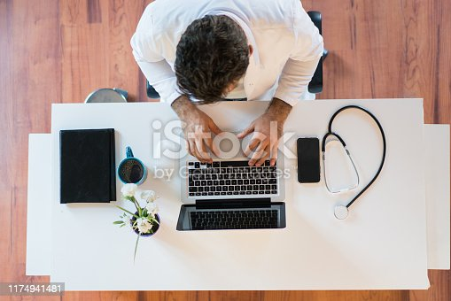 Doctor working on laptop computer in modern clinics office .