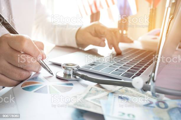 Doctor Working On Laptop Computer With Report Analysis And Money About Healthcare Costs And Fees In Medical Hostpital Office Focus Stethoscope On Table Healthcare Budget And Business Concept Stock Photo - Download Image Now