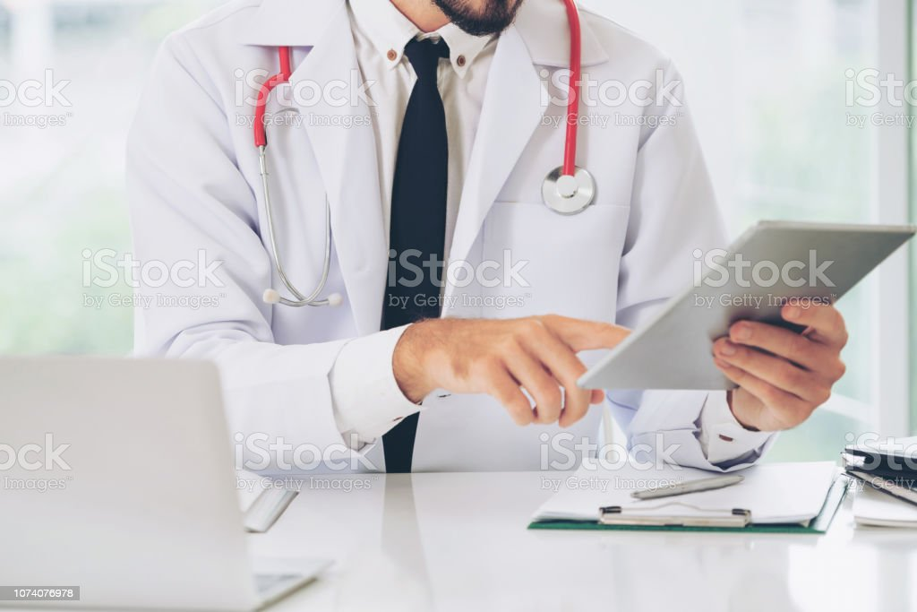 Doctor working on tablet computer at office in the hospital. Medical...
