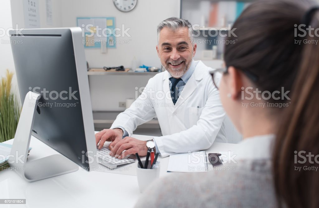 Doctor working with his computer stock photo