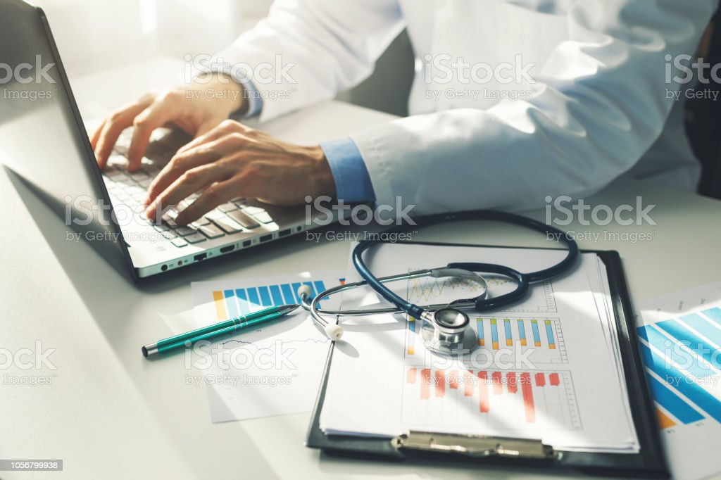 doctor working with medical statistics and financial reports in office - Стоковые фото Анализировать роялти-фри