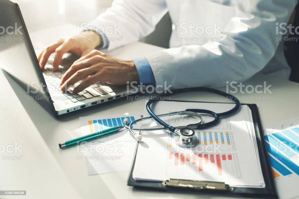 Arzt arbeitet mit Medizinische Statistik und Finanzberichte im Büro – Foto